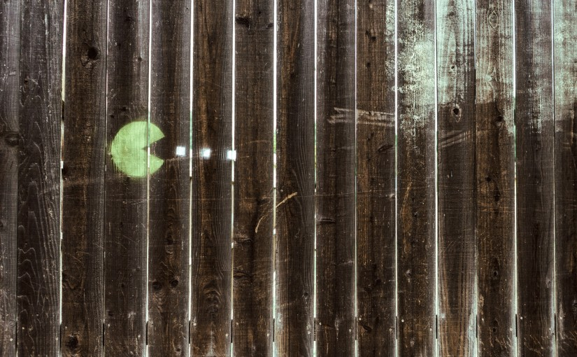 Pac-man video game graffiti on a wooden fence